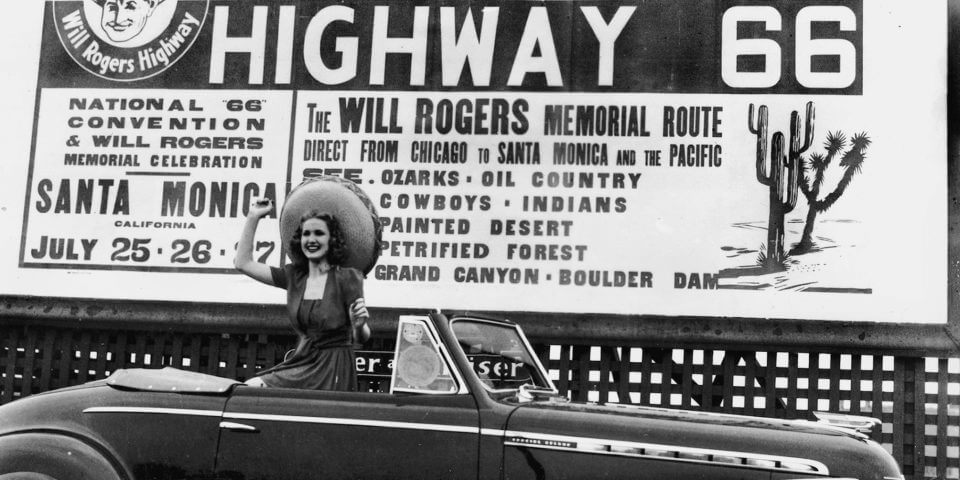 A woman sits on the backseat of an old car in front of the Highway 66 sign.