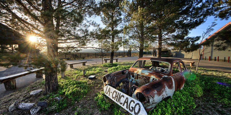 An old rusty car sits on Route 66.