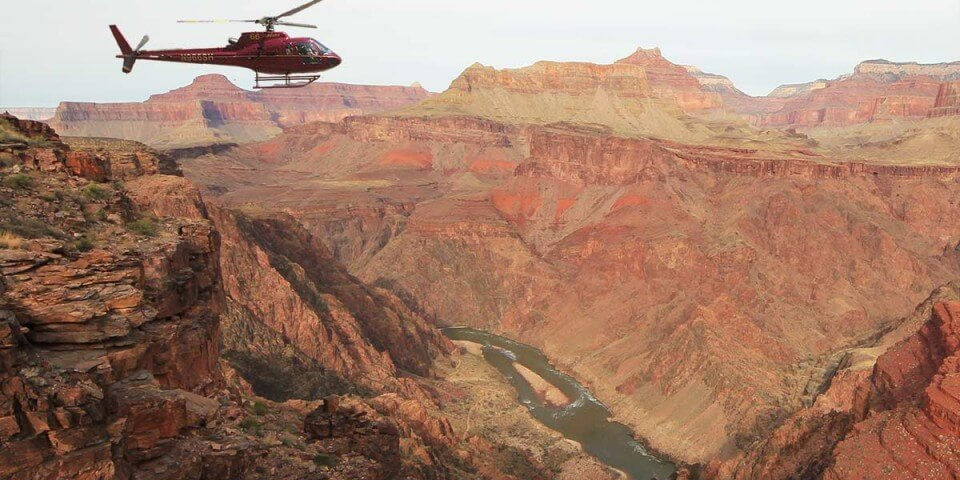 A helicopter flies over the Grand Canyon.