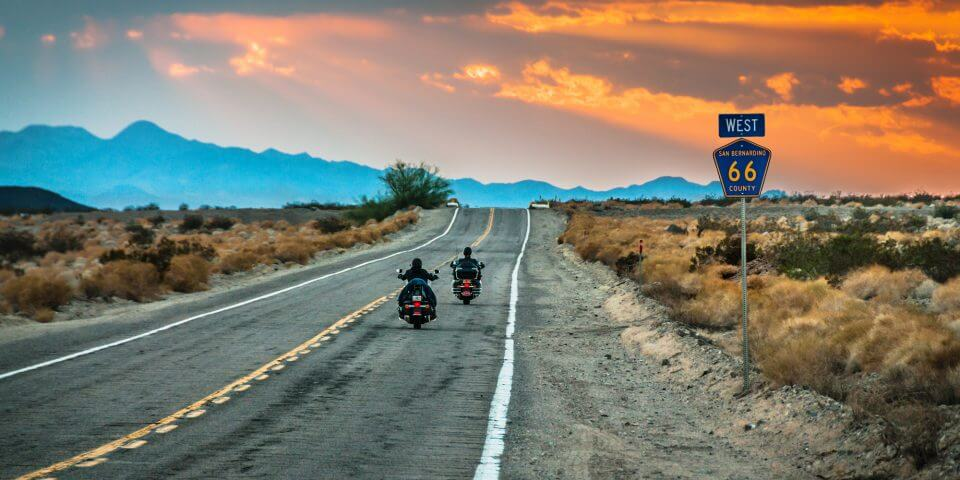 Bikers ride into the sunset on Route 66 in California.