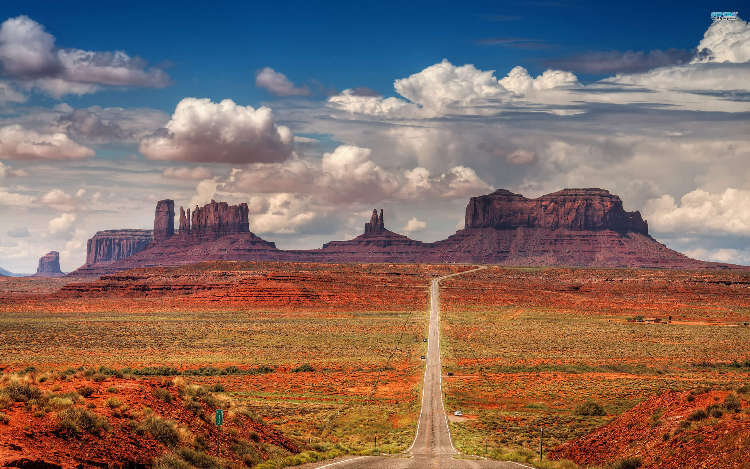 Monument Valley in the background and a road to it in the foreground.