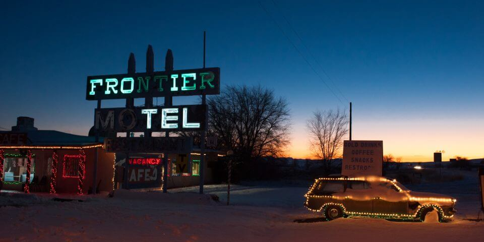 The Frontier Motel lit up at night.