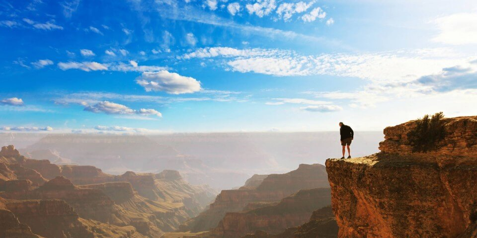 A hiker stands on the edge of the Grand Canyon.