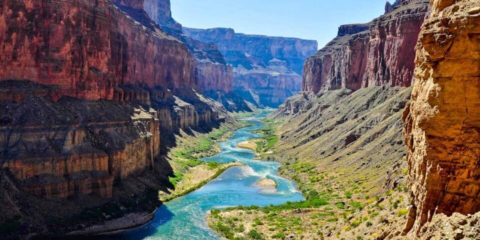 The Colorado River flowing with its blue water between the Grand Canyon.