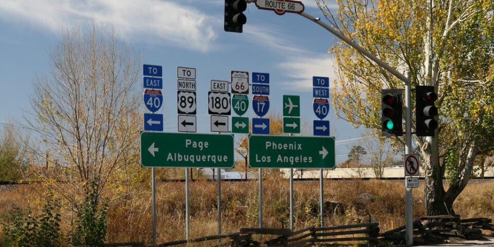 Two street signs for Page, Albuquerque, Phoenix, an Los Angeles along the hightway.