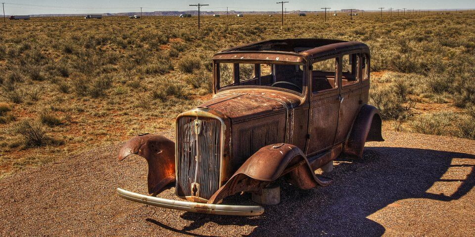An old rusted automobile sits out in the Arizona desert.