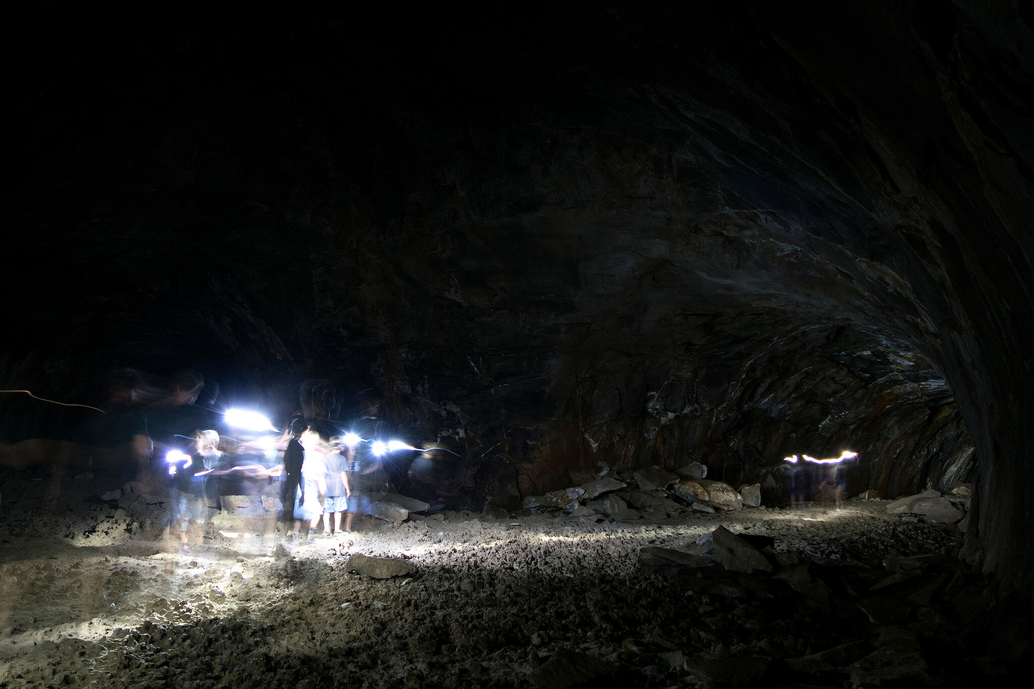 Interior of the Lava River Cave in Arizona. People are spelunking with artificial lighting. Flickr USer Nicholas Schnur