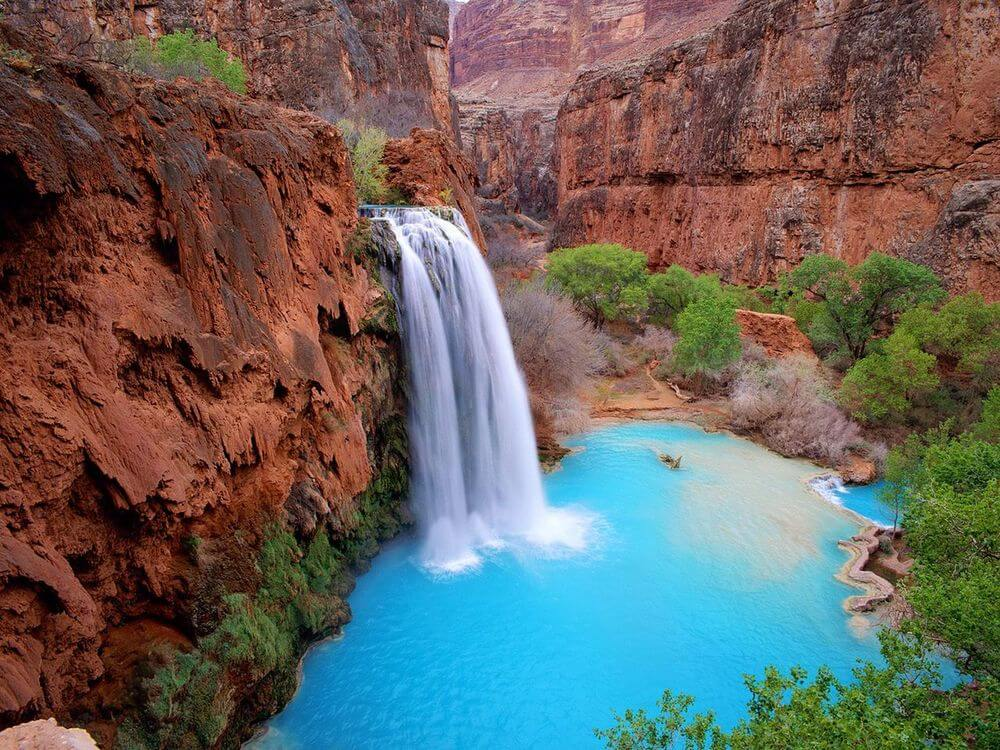 Beautiful bright blue waters as Havasu Falls pours out in the mountains.