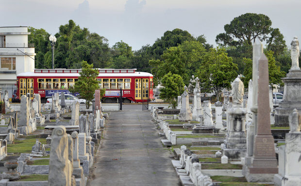 A Canal Streetcar glides along its route near the end of its line at City Park Avenue in front a haunted New Orleans cemetery.