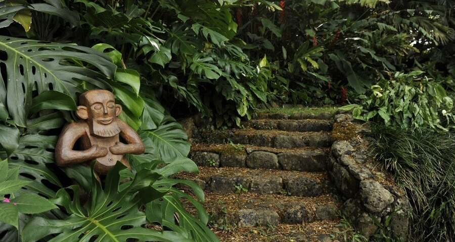 A wooden sculpture of a Menehune resting his hands on his belly next to a stone path in the Hawaiian forest.