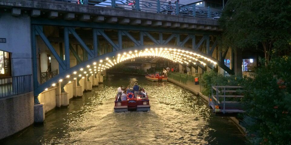 A boat goes under a lit-up bridge on along the San Antonio River. Photo by Len Radin