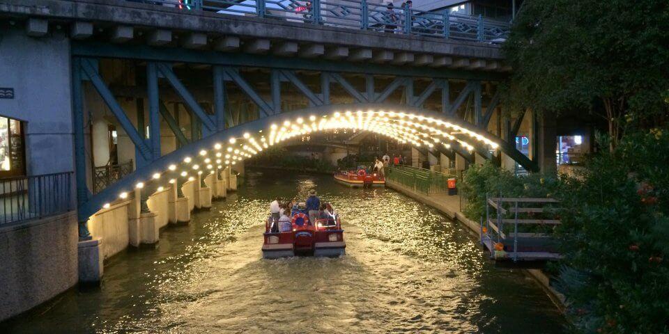 A boat goes under a lit-up bridge on along the San Antonio River. Photo by Len Radin