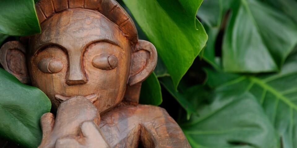 A wooden sculpture of a Menehune at a Disney resort.