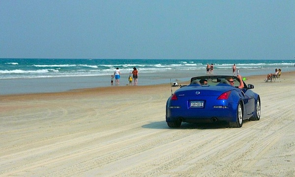 North Carolina is famous for their beaches like this one with a blue convertible driving on it.