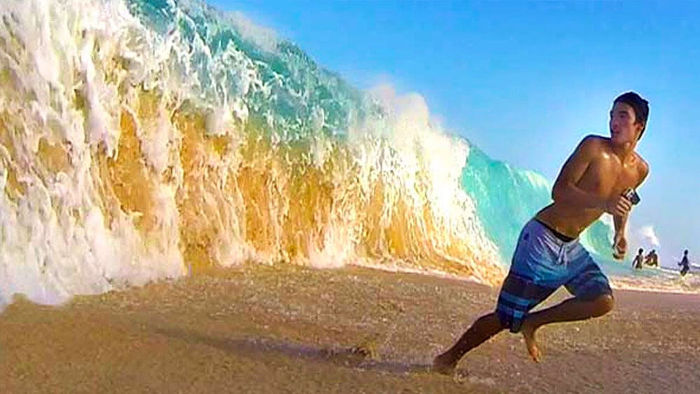 Six plus foot wave comes crashing down on the Big Beach, Maui shore as a local boy runs in the opposite direction. Very wise of him.