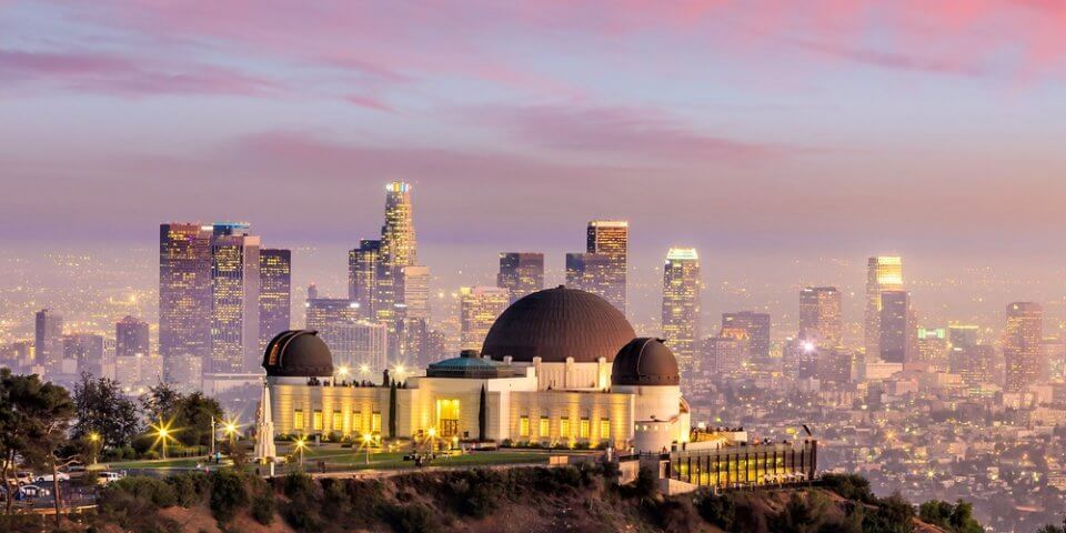 A pink skyline shot of the Griffith Observatory.