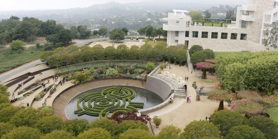 The Getty Center in Southern California. Green trees and bushes appear below a line of California mist.