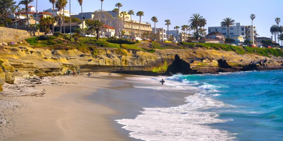 La Jolla Cove in the middle of the day with blue ocean water and surfers in the distance.