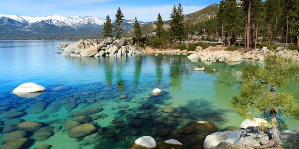 The crystal clear blue-green waters of Lake Tahoe with the Sierra Nevada mountains and trees in the background.