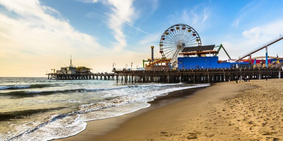Santa Monica Pier with the beach and ocean in the foreground.