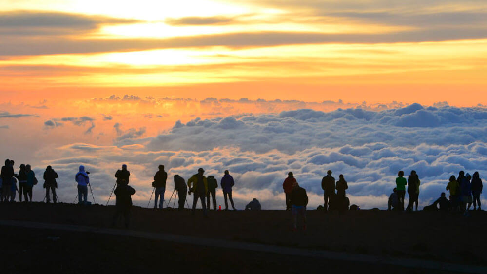 Tourists stand in a row gazing out above the clouds on Haleakala crater national park on maui hawaii