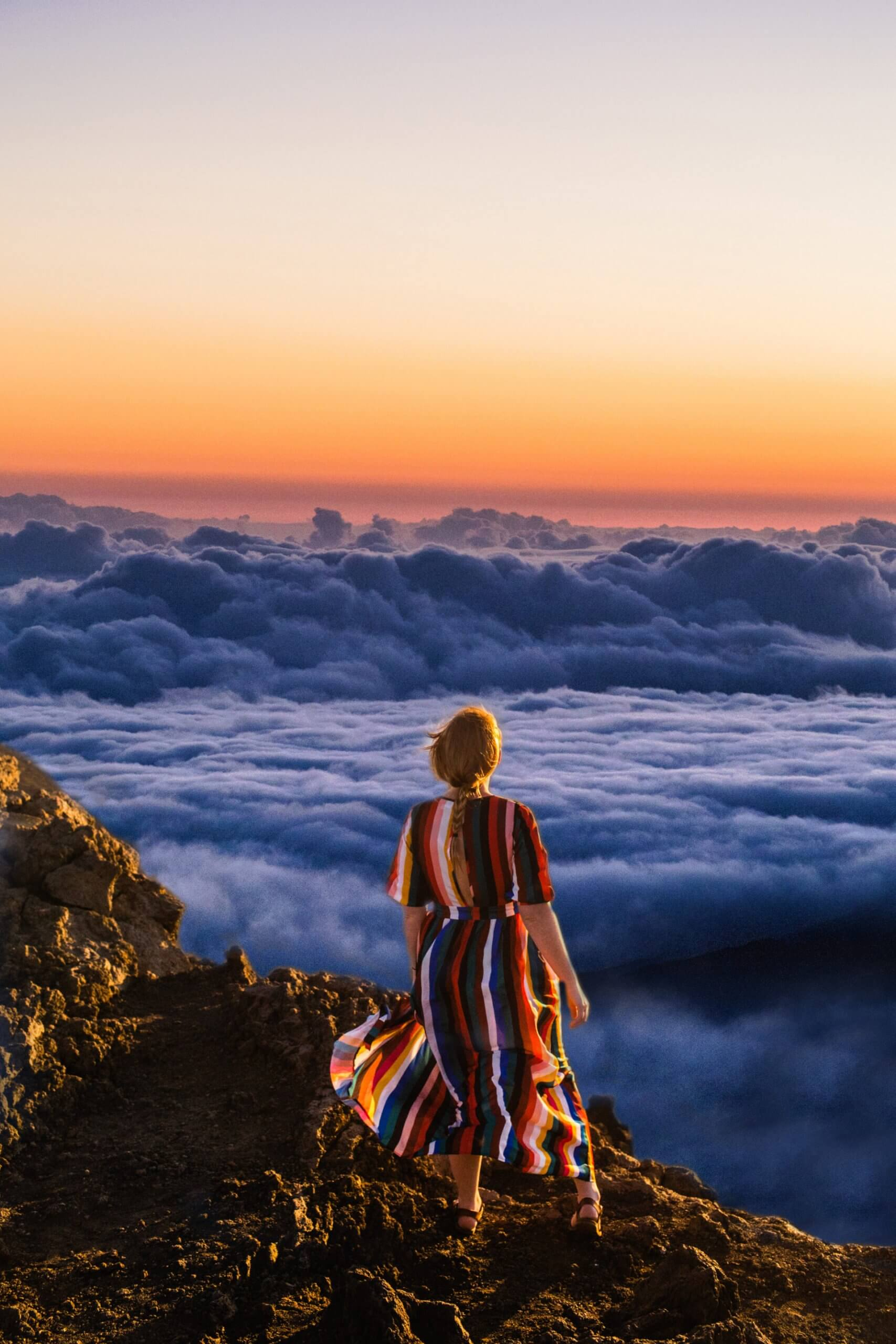 model looks over the clouds in haleakala crater on maui