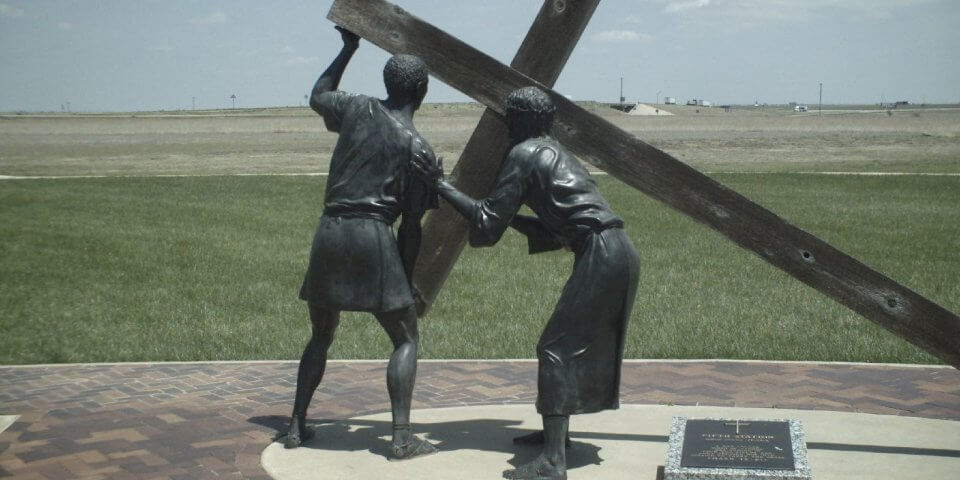 Statue of a Roman man helping Jesus carry his cross during his Crucifixion. This statue is at The Cross of Our Lord Ministries in Groom, Texas.